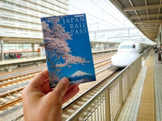 Japan-rail-pass-being-held-infont-of-the-bullet-train